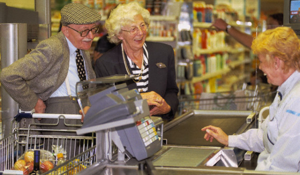 Senior Couple with Cashier at Supermarket Checkout