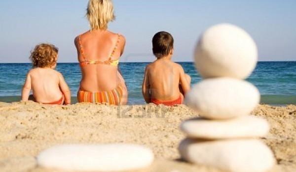 1412960-donna-e-bambini-sulla-spiaggia-in-cerca-di-sole-al-mare-incorniciato-da-ciottoli-bianchi-impilati-s