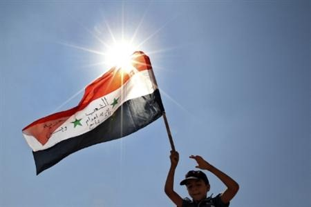 Child holds Syrian flag with Arabic words on it during a protest by Jordanians and Syrians near the city of Mafraq
