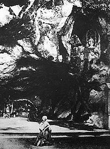 Bernadette Soubirou prega davanti alla grotta