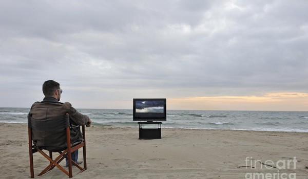 man-watching-tv-on-beach-at-sunset-sami-sarkis