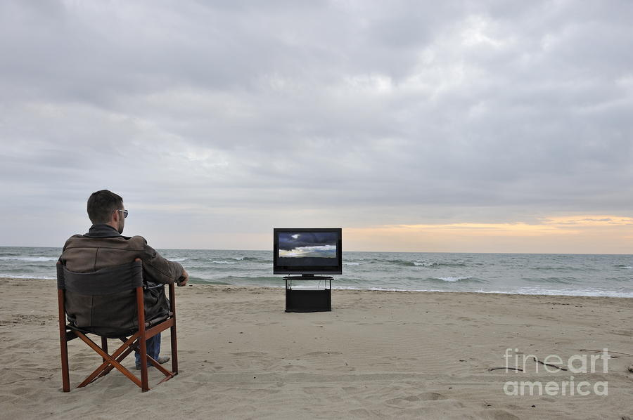 man-watching-tv-on-beach-at-sunset-sami-sarkis