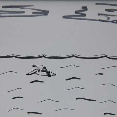 Pelican gliding over ocean
