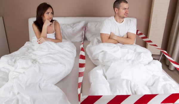 Angry young man lying separately from wife on the bed